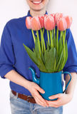 Woman holding jug with tulips Stock Images