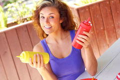 Woman Holding Ketchup And Mustard Bottles Royalty Free Stock Image