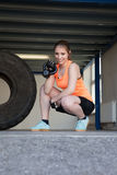 Woman holding a kettlebell and smiling to camera - fitness Stock Photo