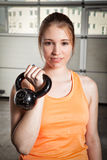 Woman holding a kettlebell and smiling to camera - fitness Royalty Free Stock Photo