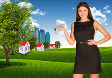 Woman holding key. Skyscrapers and houses with Royalty Free Stock Image