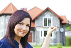 Woman holding keys with house background stock photo