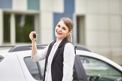 Woman holding keys to new car auto and smiling at camera royalty free stock photo