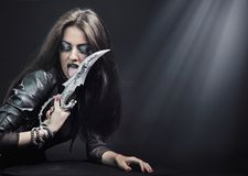 Woman holding a knife. Rock-star woman holding a knife stock images