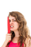 Woman is holding a knife close to her face Stock Photo