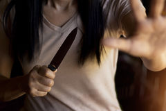 Woman holding a knife in hand while defending herself. From attacks stock images