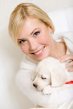 Woman holding labrador puppy with red ribbon Royalty Free Stock Photo