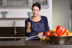 Woman Holding Ladle While Reading a cookbook Royalty Free Stock Image