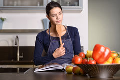 Woman Holding Ladle While Reading a cookbook Stock Photo