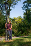 Woman holding lamp post Stock Photos
