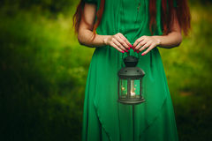 Woman holding lantern with candle. Woman with long red hair holding lantern with burning candle in forest. Concept of fairy-tale, mystery, fantasy royalty free stock image
