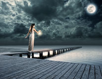 Woman holding a lantern on a wharf Royalty Free Stock Photography