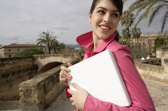 Woman Holding Laptop. Beautiful young woman turning around while holding a laptop computer un her arms Royalty Free Stock Photo