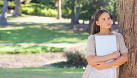 Woman holding a laptop. While leaning against a tree royalty free stock photography