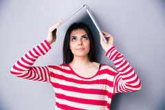 Woman holding a laptop above her head like a roof Stock Images
