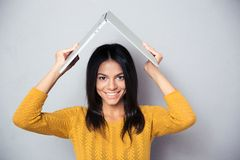 Woman holding laptop above her head like a roof Royalty Free Stock Photos