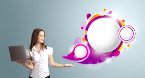Woman holding a laptop. Attractive young woman holding a laptop and presenting abstract speech bubble copy space royalty free stock image