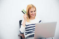 Woman holding laptop and bank card Royalty Free Stock Image