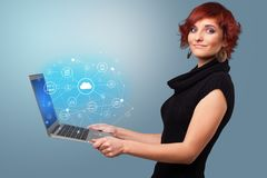 Woman holding laptop with cloud based system concept. Woman holding laptop projecting cloud based system symbols and informations stock photos