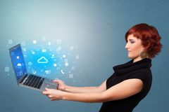Woman holding laptop with cloud based system notifications. Woman holding laptop projecting notifications, symbols and information based on cloud technology stock photography