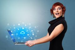 Woman holding laptop with cloud based system notifications. Woman holding laptop projecting notifications, symbols and information based on cloud technology stock image