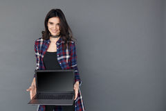 Woman holding a laptop computer with black empty screen. Happy woman holding a laptop computer with black empty screen  over grey background and copyspace Royalty Free Stock Photography