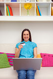 Woman holding laptop and credit card. Smiley young woman holding laptop and credit card royalty free stock photography