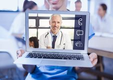 Woman holding a laptop with doctor on video call screen. At clinic Royalty Free Stock Photo