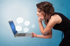 Woman holding laptop with speech bubbles. Woman holding laptop with a few speech bubble symbols royalty free stock photo