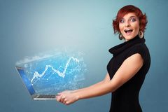 Woman holding laptop with financial concept. Woman holding laptop projecting financial information, diagrams and charts royalty free stock photos