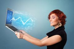 Woman holding laptop with financial concept. Woman holding laptop projecting financial information, diagrams and charts royalty free stock images