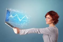 Woman holding laptop with financial concept. Woman holding laptop projecting financial information, diagrams and charts n royalty free stock photography