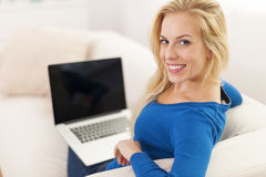 Woman holding laptop on knees Stock Photography