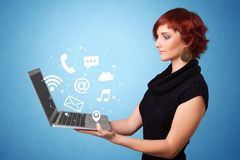 Woman holding laptop with online symbols. Woman holding laptop with online services symbols royalty free stock image