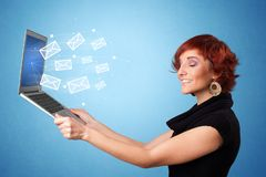 Woman holding laptop with online symbols. Woman holding laptop with online services symbols royalty free stock photos