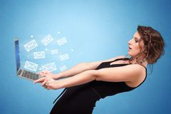 Woman holding laptop with online symbols. Woman holding laptop with online services symbols royalty free stock photo