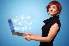 Woman holding laptop with online symbols. Woman holding laptop with online services symbols royalty free stock photography