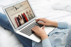 Woman holding laptop with open beauty blogger site on bed. Closeup stock image