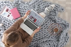 Woman holding laptop with open beauty blogger site on floor. Top view stock photos