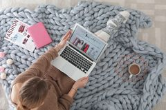 Woman holding laptop with open beauty blogger site. On floor, top view stock image