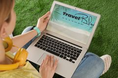 Woman holding laptop with open travel blogger site on artificial grass. Closeup royalty free stock photos