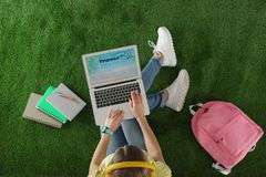 Woman holding laptop with open travel blogger site on artificial grass. Top view royalty free stock photography