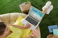 Woman holding laptop with open travel blogger site on artificial grass. Above view royalty free stock photo