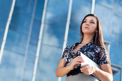Woman holding laptop over glass building. Beautiful woman holding laptop over glass building background royalty free stock photos