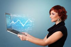 Woman holding laptop with financial concept. Woman holding laptop projecting financial information, diagrams and charts n stock image
