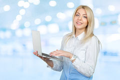 Woman holding laptop. Smiling business woman holding laptop royalty free stock image