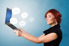 Woman holding laptop with speech bubbles. Woman holding laptop with a few speech bubble symbols stock photography