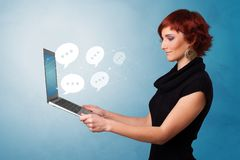 Woman holding laptop with speech bubbles royalty free stock images
