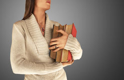 Woman holding large books. A studio view of a young woman holding several large, heavy books.  Grayish background Stock Photos