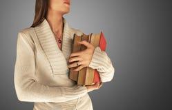 Woman holding large books Stock Photos